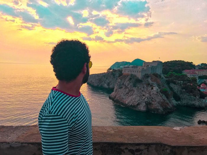 Side view of man looking at sea against sky during sunset