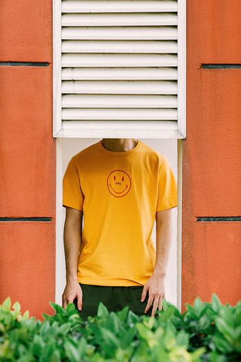 Midsection of man standing against yellow wall