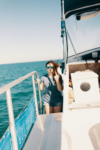 Young woman on boat in sea against sky