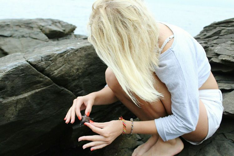 Side view of young woman holding starfish while sitting on rock formation