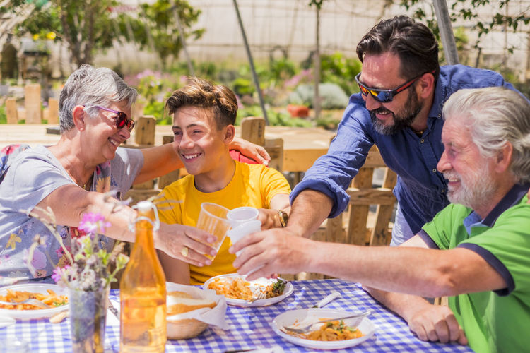 Happy family toasting drinking glasses at restaurant