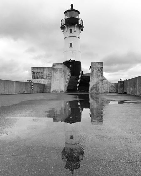 View of lighthouse by building against cloudy sky