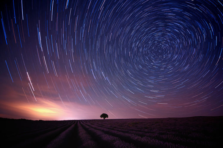 Star trail over field against sky at night