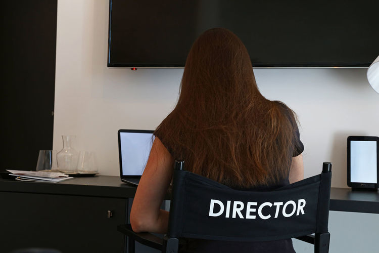 Rear view of director sitting on chair at office