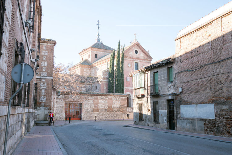 Alcala de henares, madrid, Spain-FEBRUARY 25, 2017. View of the Trinidad street. In the background the convent of the trinity Architecture Building Exterior Built Structure City Cityscape Clock Day Medieval No People Outdoors Place Of Worship Religion Sky Spirituality Street Travel Destinations