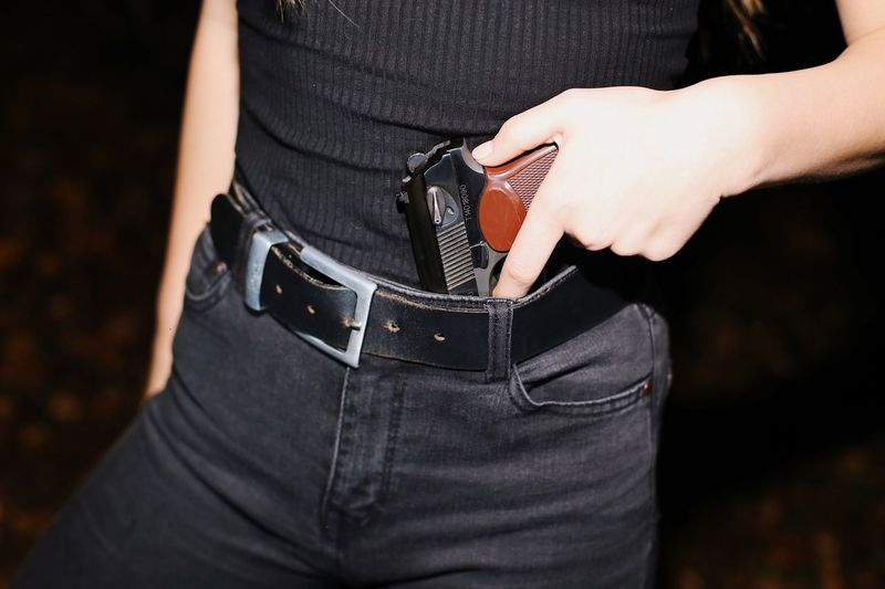 Midsection of woman holding handgun at night