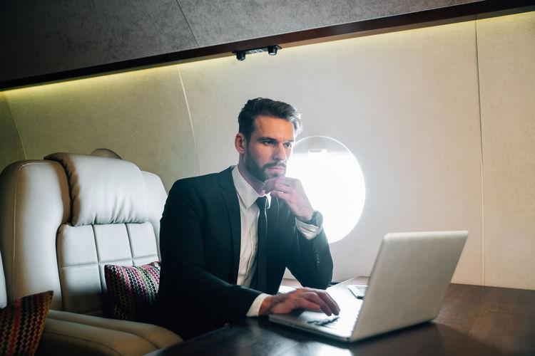 Businessman using laptop in airplane
