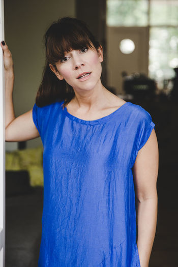 Angry Home Looking At Camera Standing Bangs Blue Brown Hair Casual Clothing Day Front View Lifestyles One Person Real People Sceptical Window Young Woman