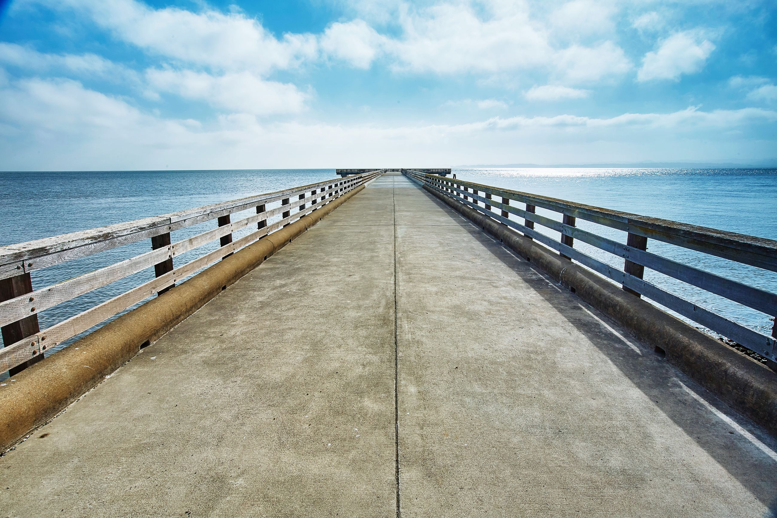 sea, horizon over water, water, sky, the way forward, diminishing perspective, cloud - sky, pier, tranquil scene, railing, tranquility, cloud, scenics, blue, beach, long, vanishing point, beauty in nature, nature, cloudy
