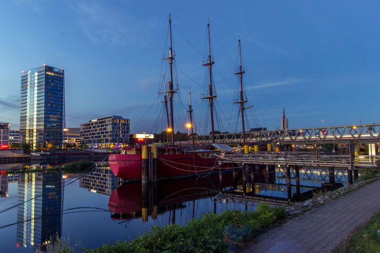 Boat moored on river in city at dusk
