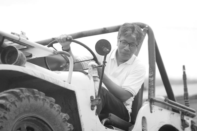 Low angle view of mature man driving off-road vehicle against sky