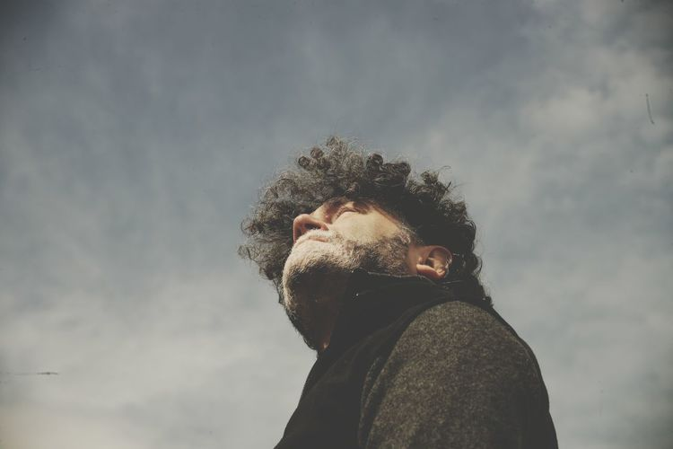 Low angle view of man looking at camera against sky