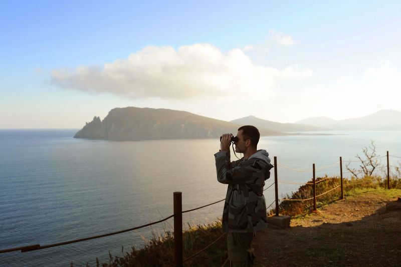 Man in gray military jacket looks  binoculars on high altitude mountain surrounded by sea, mountains
