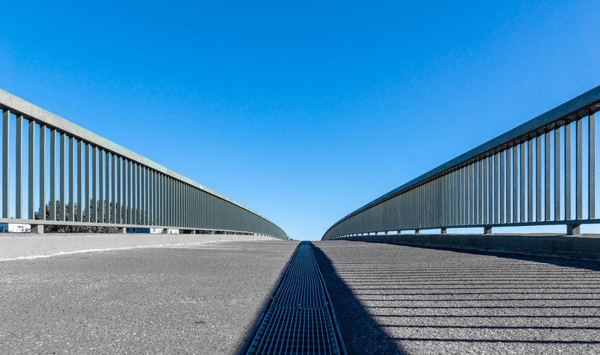 Surface level of empty bridge against clear blue sky