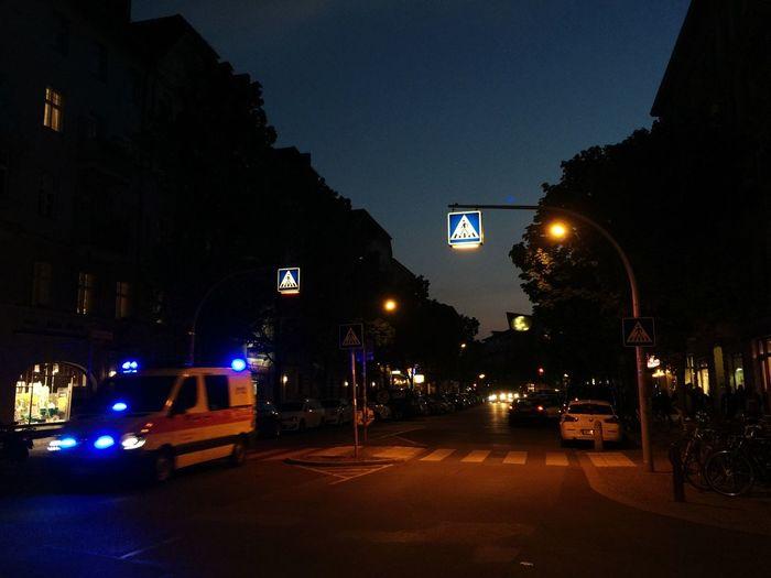 Illuminated road against sky in city at night