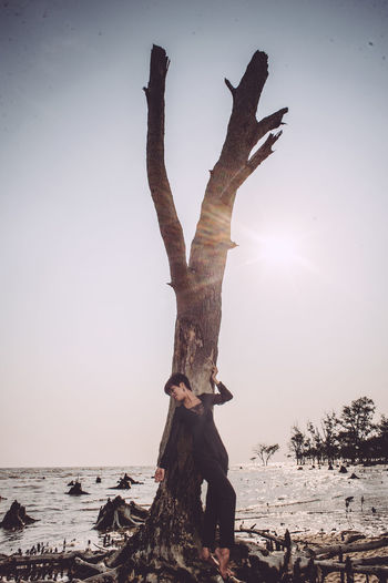 Woman Standing Against Driftwood At Beach Against Sky