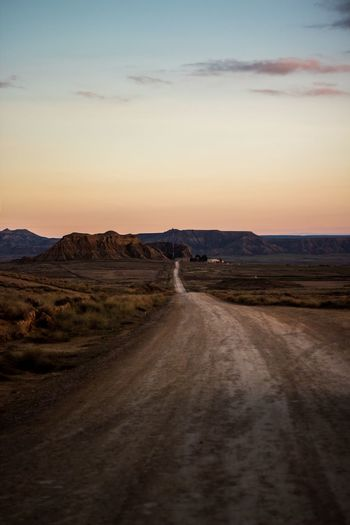 Dirt Road Leading Towards Against Sky During Sunset
