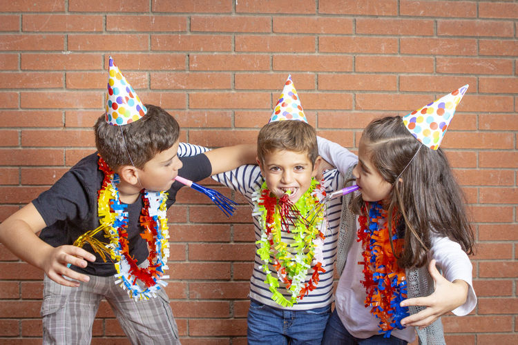 Portrait of siblings wearing garlands and party hats against brick wall