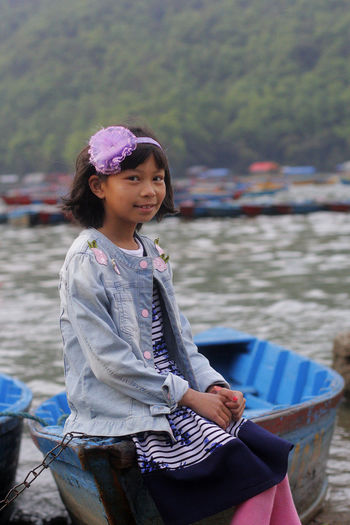 Portrait of smiling girl sitting on paddle boat at lakeshore