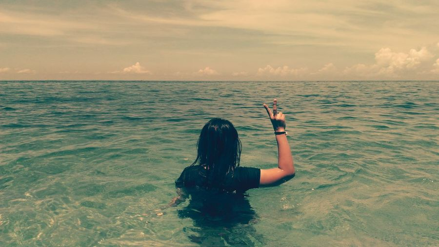 Rear View Of Woman In Sea Showing Peace Sign Against Sky