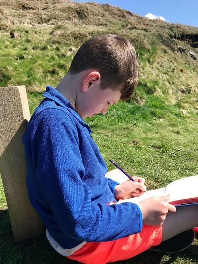wherever we go he will draw Boy Sat On The Coast Drawing At One With The Outdoors Old Skool Drawing Pen And Paper No Technology Cornish Coastline Sitting Grass Close-up Casual Clothing Personal Perspective Low Section Calm 50 Ways Of Seeing: Gratitude