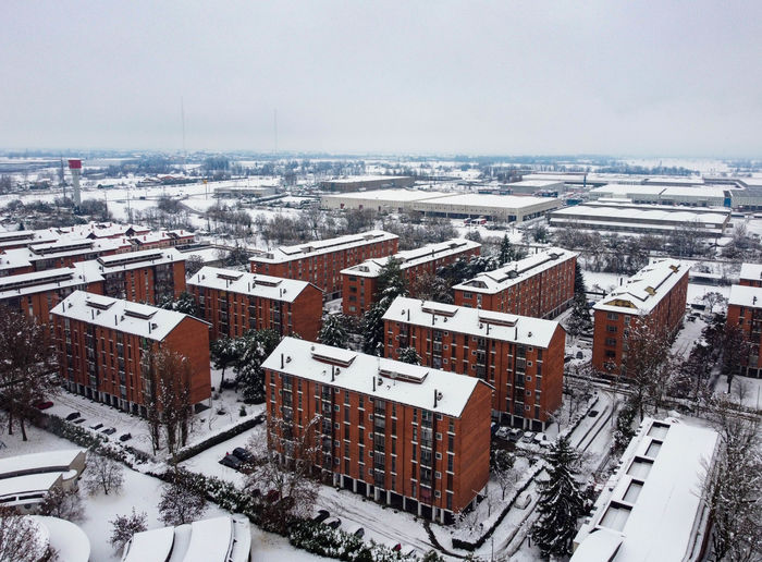 High angle view of snow covered buildings in city against sky