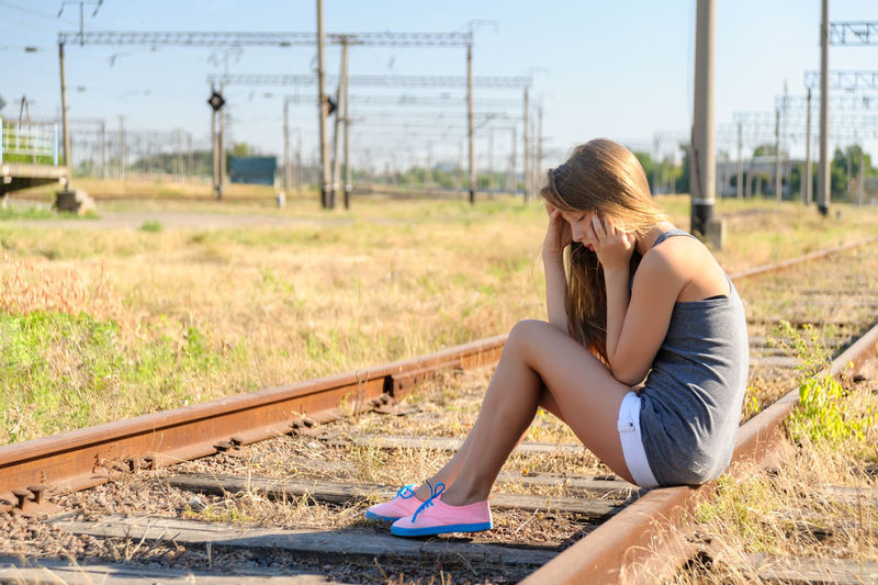 Sad girl teenager sitting on rusty rail track outside the town. Escape to be alone Blonde Caucasian Day Female Girl Horizontal Lonely Outdoors Outskirts Problem Rail Rural Shorts Sit Summer Teen Teeneger Town Track Upset