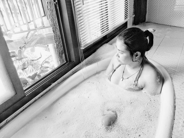 Thoughtful young woman in bathtub at home