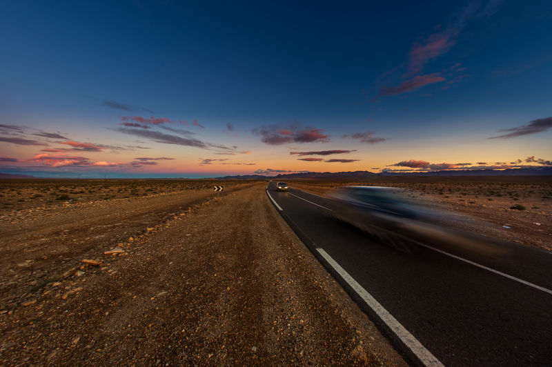 Car in a highway in Morocco far from Marrakesh Sky Road Cloud - Sky Sunset Direction The Way Forward Transportation Nature Horizon vanishing point No People Land Landscape Scenics - Nature Environment Sign Tranquility Tranquil Scene Outdoors Horizon Over Land Dividing Line