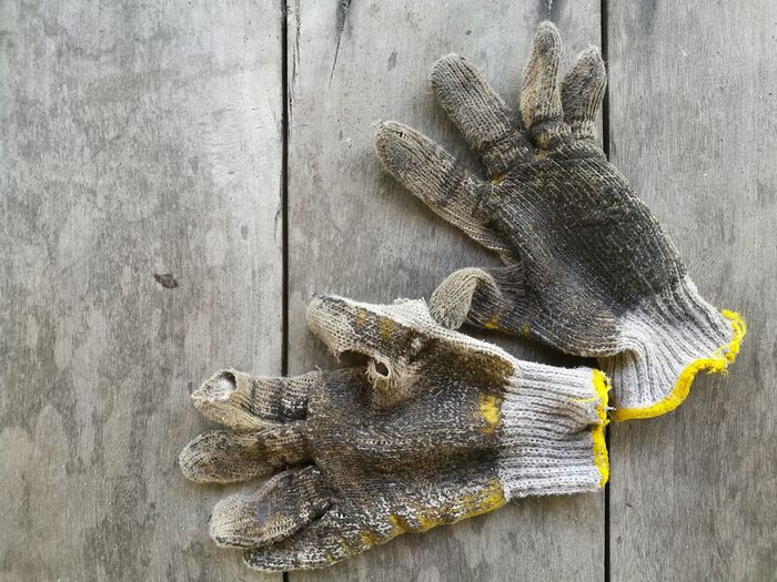 High Angle View Of Messy Mechanic Gloves On Table