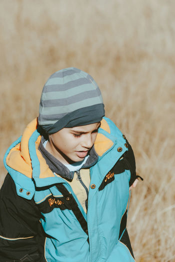 Boys Childhood Close-up Day Field Focus On Foreground Front View Knit Hat Leisure Activity Lifestyles Looking Down Nature One Person Outdoors People Real People Warm Clothing Young Adult Young Women