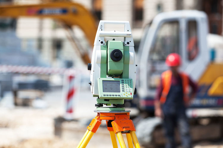 Surveyor equipment tacheometer or theodolite outdoors, at a construction site Focus On Foreground Technology Machinery Equipment Safety Occupation Close-up Tripod Industry Outdoors Engineering Theodolite Construction Construction Site Construction Industry Civil Engineering Surveying Site Building Survey Geodesy Land Measuring Surveyor Fieldwork Measurement Workplace Activity Constructing Checking Digging Geometery Geometer Examination Geodesist Ground Helmet Instrument Machine Position Planning precision Topographic Worker Protective Workwear Protective Tool