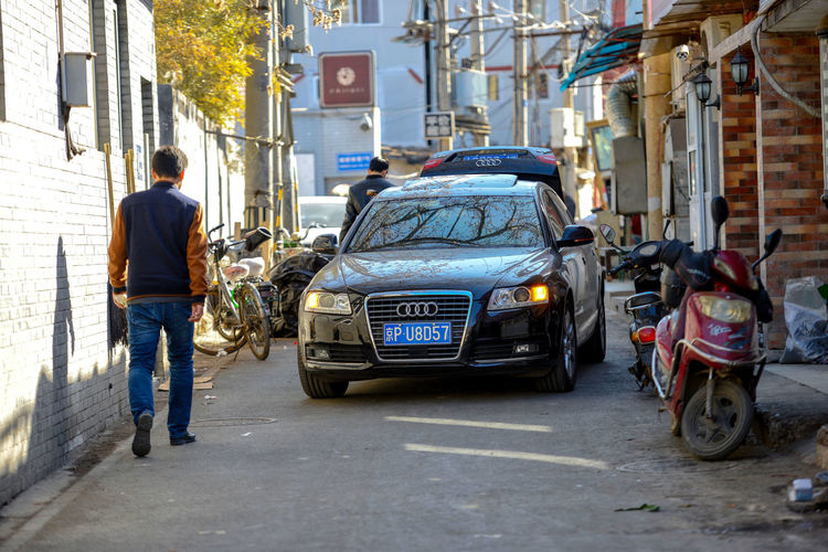 BEIJING, CHINA - MARCH 10, 2016: The old Beijing hutong with its narrow streets, with its exotic and modern vehicles. ASIA Beijing Cars Cityscape Delivery Peking  Scooter Service Tourists Traffic Travel Capital China City Life Culture Destination Hutong Hutong Life Hutong Street Land Vehicle Mode Of Transportation Street Transportation Urban