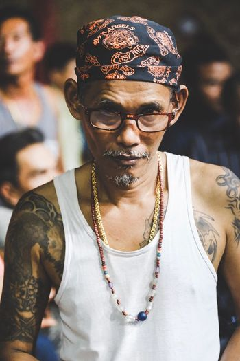 Gambling master at the Thai Boxing Event Gold Bandana Rough Tattoo Gangster Thailand EyeEm Selects One Person Front View Real People Fashion Lifestyles Inner Power Young Adult Portrait Casual Clothing Glasses Focus On Foreground Necklace Jewelry Waist Up Looking At Camera Young Men Sunglasses Indoors  Bandana Day This Is Aging Focus On The Story