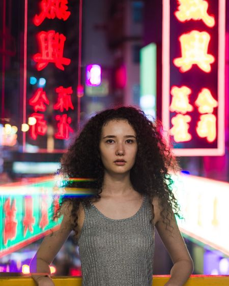 Front View Portrait Looking At Camera Curly Hair Long Hair Young Adult Women Who Inspire You EyeEm Selects Portrait Of A Friend City Urban Hong Kong Urban Exploration Looking At Camera City Life Neon Lights Lights City Lights Night Lights One Person Close-up Fashion Photography Young Women Portrait Of A Woman Cityscape