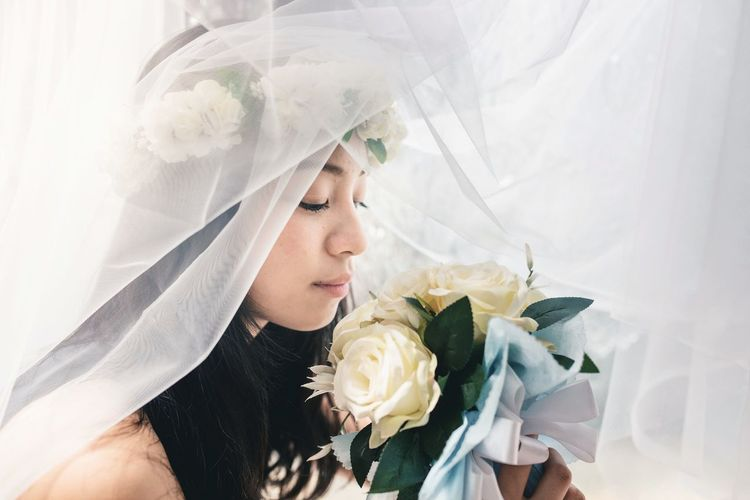 Close-Up Of Bride Smelling Flower Bouquet