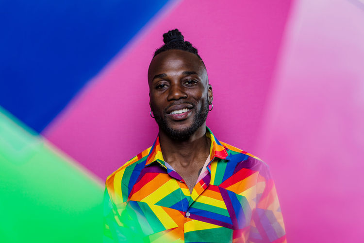 Portrait of young man standing against multi colored background