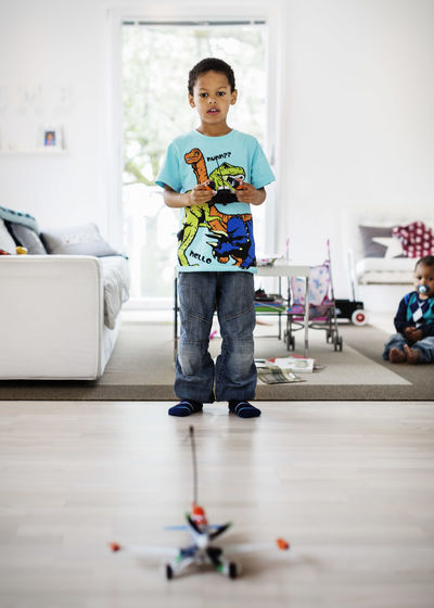 Portrait of smiling boy standing on floor at home