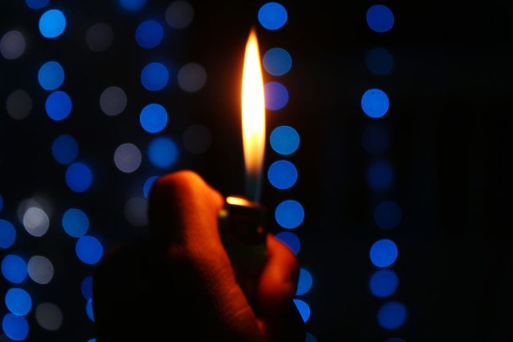 Close-Up Of Hand Holding Illuminated Cigarette Lighter At Night