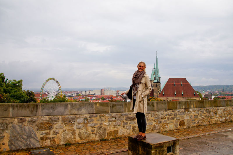 Woman Standing On Seat Against Cityscape