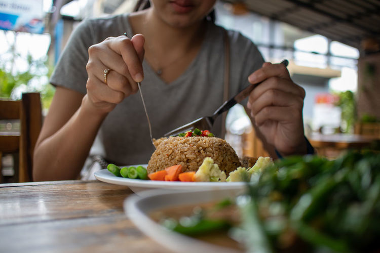 Midsection of woman eating thai food in restaurant.