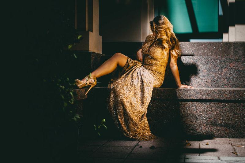 Female model in golden dress sitting on seat