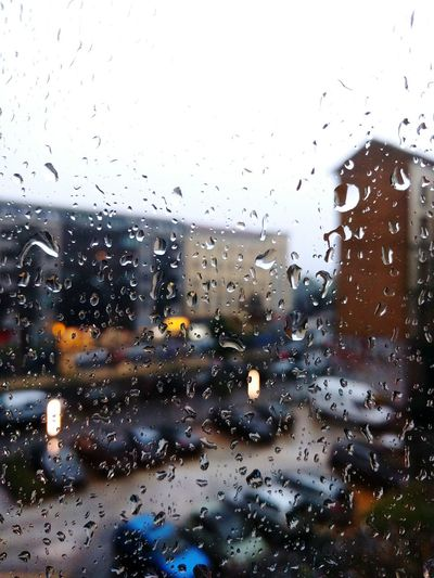 Vehicles at parking lot against clear sky seen through wet glass window during monsoon