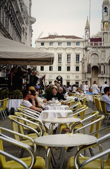 Adult Architecture Arrangement Building Exterior City Hanging Out Large Group Of People Outdoors People Sitting Sitting Outside Table And Chairs Table Arrangement Tables Teatime Women