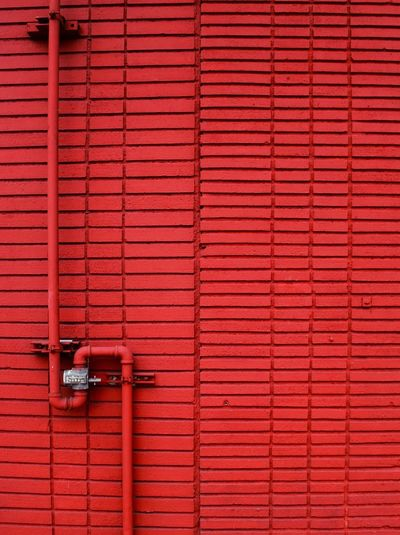 Metallic Pipe Against Red Wall
