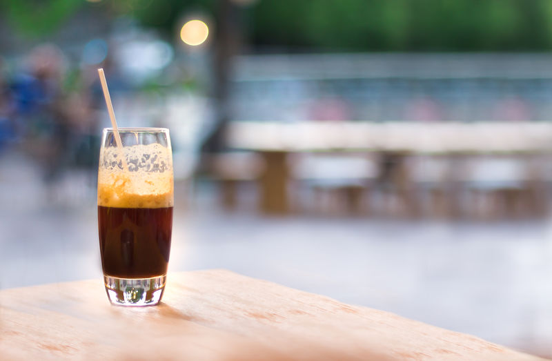 Beverage Blurred Background Brown Caffeine Coffee Cold Drink Drinks Espresso Foam Frappe Freddo Glass Greece Greek Ice Iced Isolated No People Refreshment Sea Skópelos Straw Summer Table Vacation Wooden Table