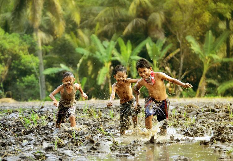 Shirtless boys running in muddy water