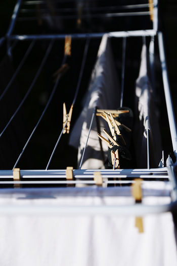 Close-up of wooden clothespins on a rack standing outdoors in light and shadows