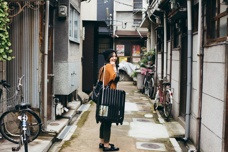 A woman holding a suitcase in the street