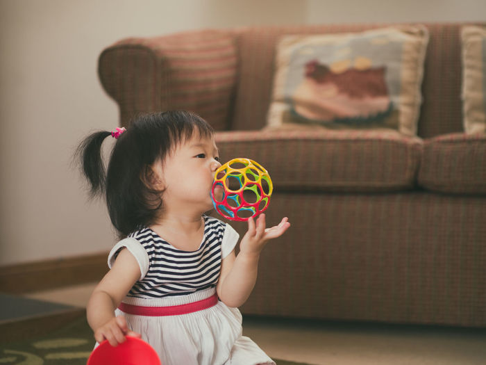 teething baby girl playing at home Asian Baby Girl Bubble Wand Casual Clothing Childhood Day Focus On Foreground Girls Holding Home Interior Indoors  Leisure Activity Lifestyles Living Room One Person People Playing Real People Sofa Teething Baby
